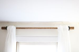 wood curtain rod with black brackets and white sheer curtains