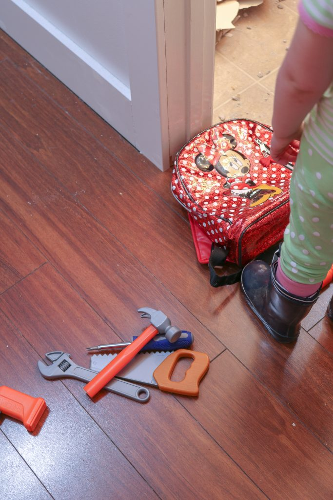play toys in floor with toddler's leg and minnie mouse backpack