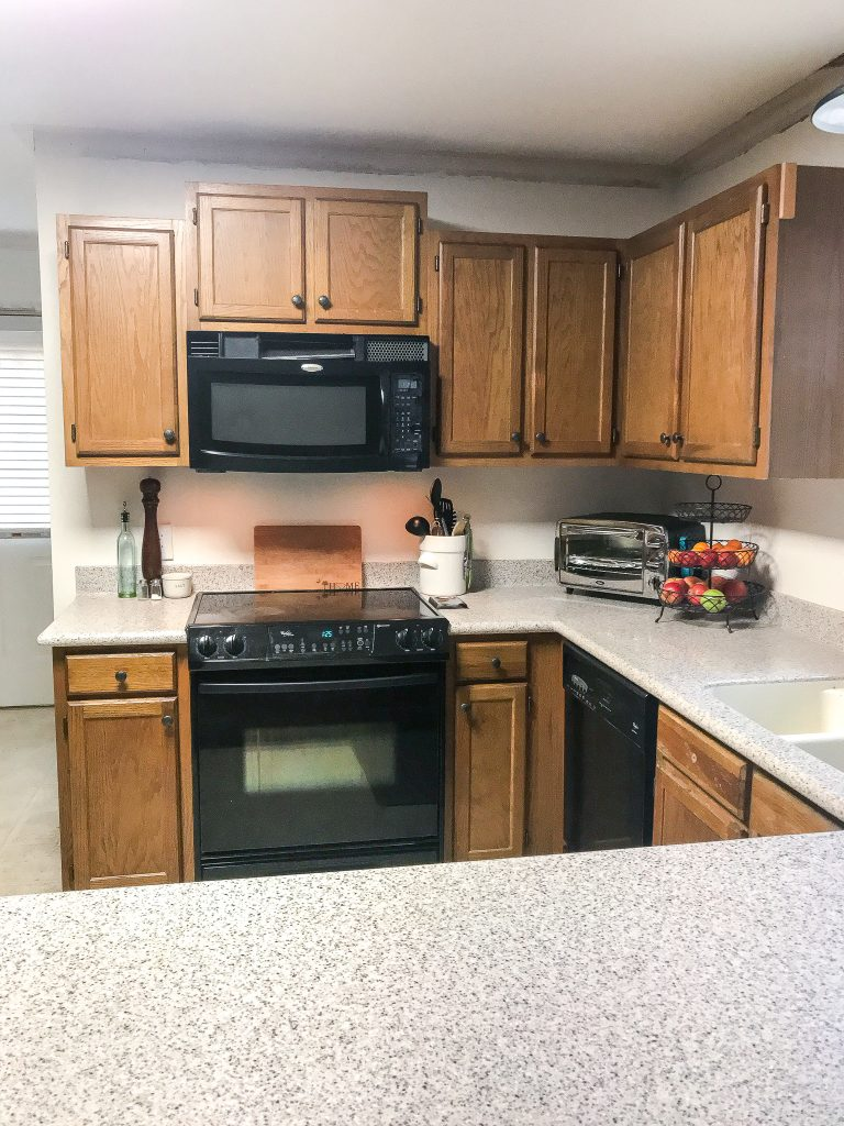black appliances and orange brown wood cabinets in a kitchen