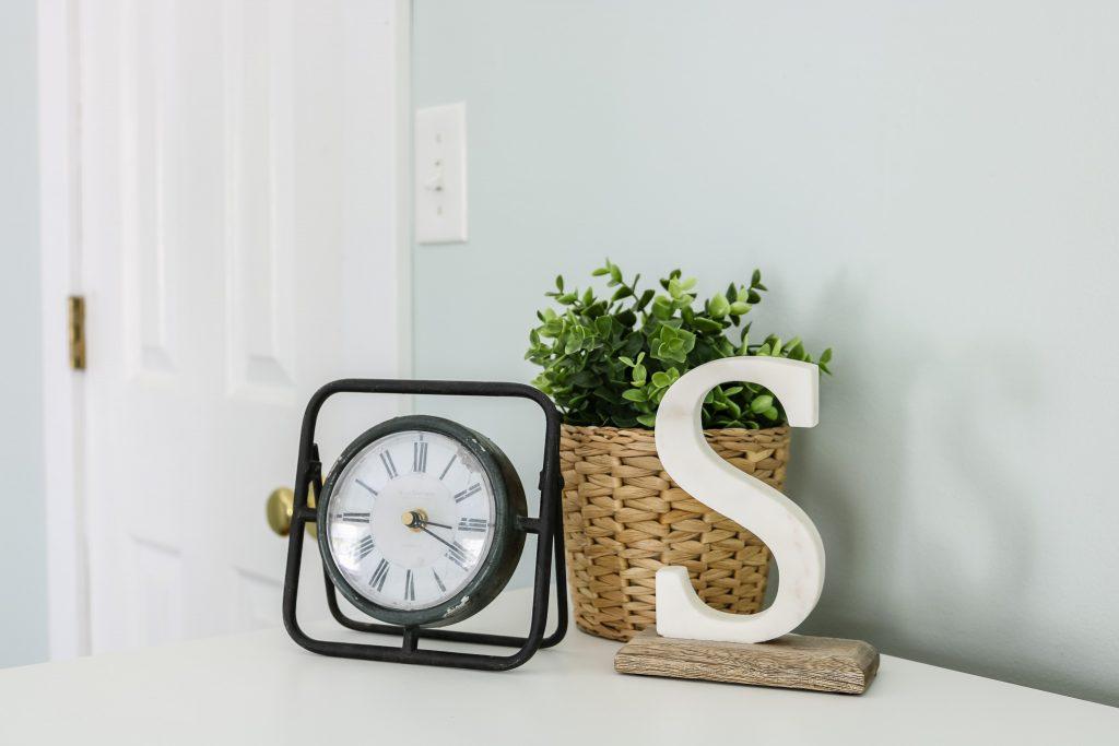 closeup of marble S and clock on white Ikea Hemnes dresser