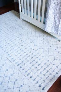 white and gray geometric rug with white crib