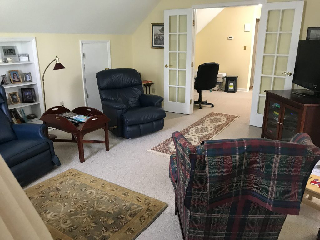 playroom with yellow wall and recliner in the corner