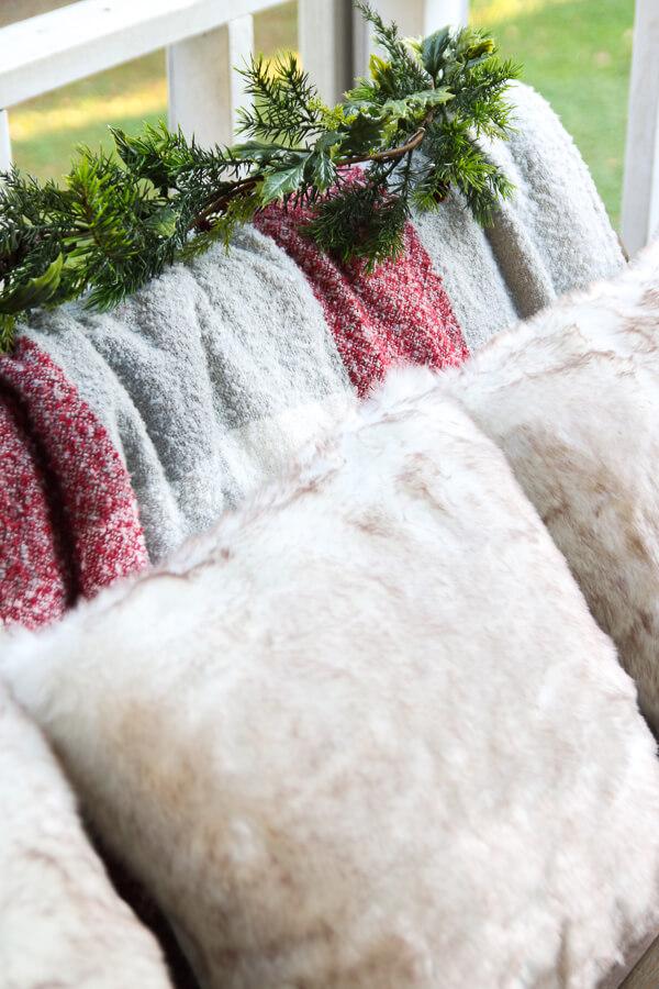 closeup of 3 fuzzy pillows and buffalo check fuzzy blanket