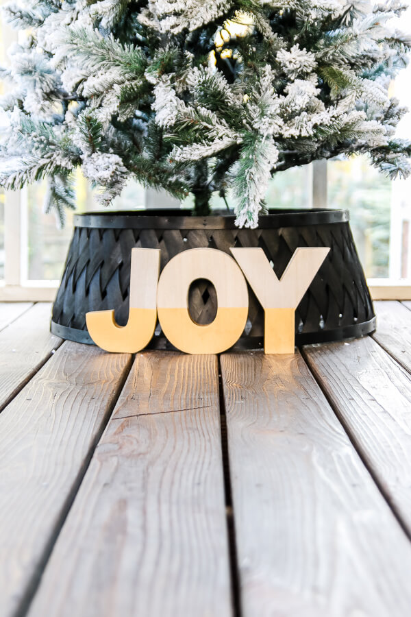 wood joy letters at base of white flocked christmas tree and black christmas tree collar