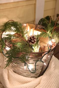 christmas lights and pinecones in a galvanized bucket