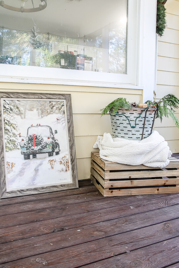 galvanized bucket on porch with white blanket wrapped around it next to car in the snow painting