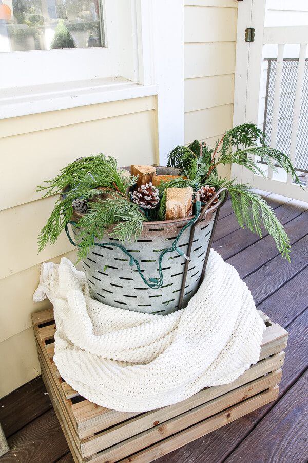 galvanized bucket on porch with white blanket wrapped around it