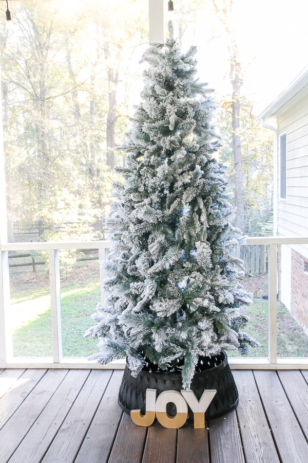 white flocked christmas tree with black tree collar