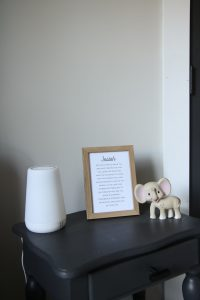 rest sound machine and kiki elephant on gray side table in nursery