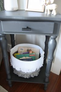 gray side table in nursery with basket of books underneath