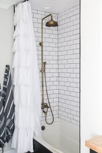 white and black bathroom with white subway tile with black grout