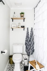 white bathroom with black and white patterned tile and turkish towels hanging on the wall with open wood shelves over the toilet
