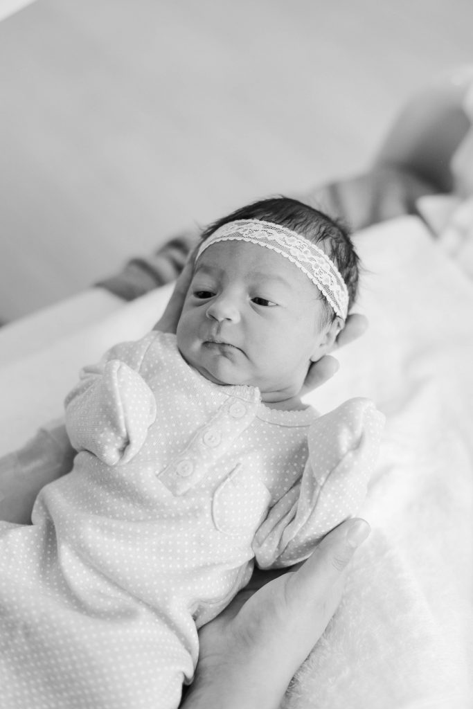 black and white photo of baby girl in white lace headband