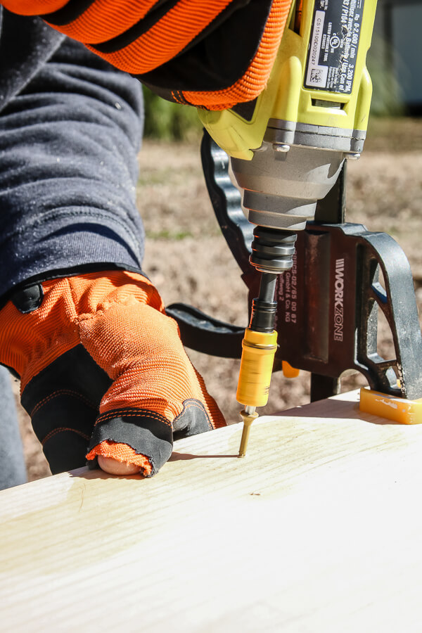 man's hand with orange glove and impact driver into wood