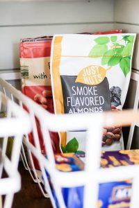 Aldi smoke flavored almonds in white metal organizing basket