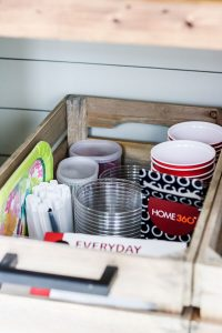 party supplies in wood crate in bottom of organized pantry