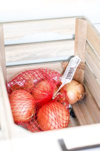 bag of onions in crate on casters