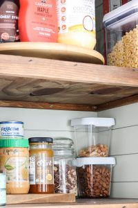 clear plastic containers with white lids in small pantry closet