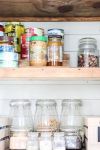 organized glass hocking jars in pantry with shiplap