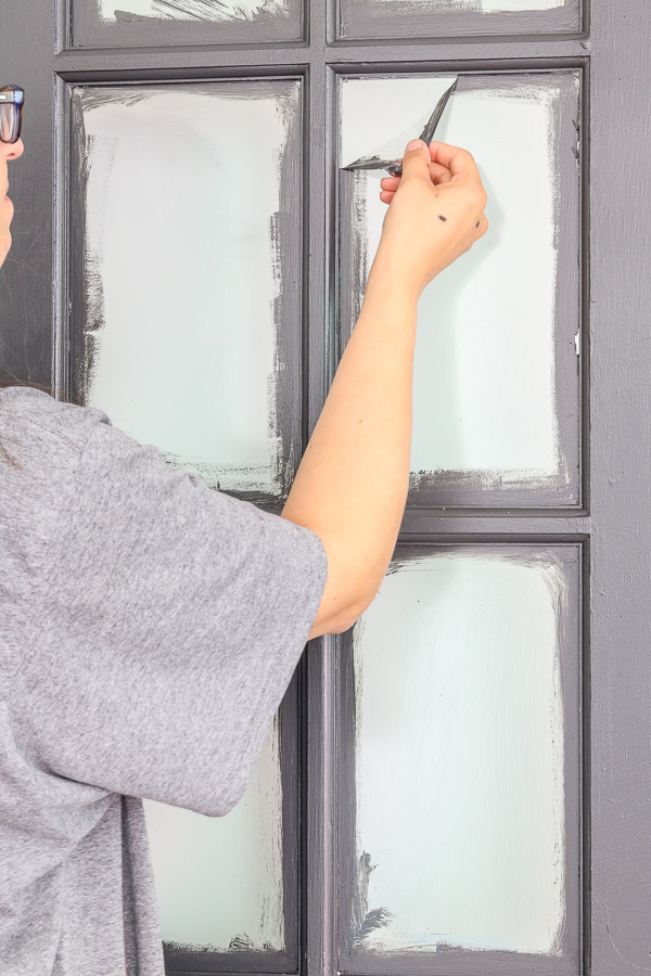 woman in gray shirt pulling off film of painted french doors