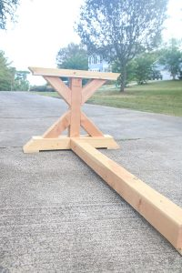 farmhouse table leg attached to bottom foot rest board