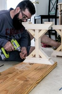 man with beard and glasses drilling in x shaped foot to the base of a farmhouse table bench