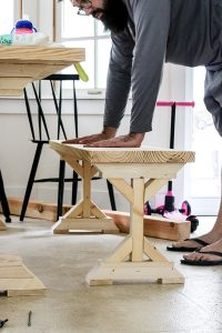 man with 2 hands on the farmhouse table bench unstained