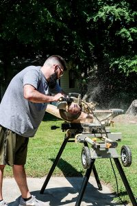 man with beard using table saw to cut scrap wood