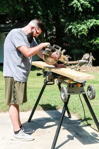 man with table saw cutting lumber boards