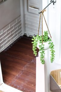 faux hardwoods and faux hanging succulent in front of little tikes playhouse makeover