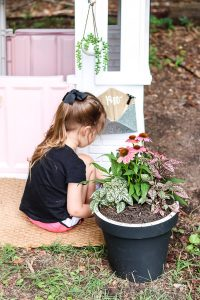little girl playing in front of playhouse