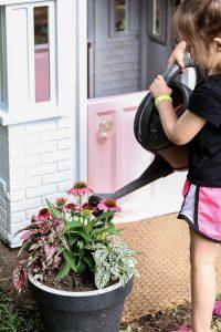 little girl watering flowers outside little tikes playhouse