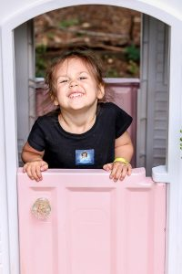 little girl smiling in playhouse makeover