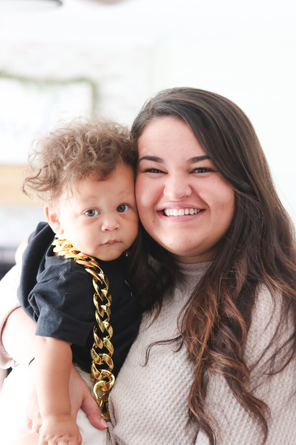 brunette holding baby boy with gold chain