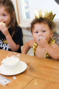 boy with no shirt and gold crown and chain eating birthday cake 1st birthday white smash cake