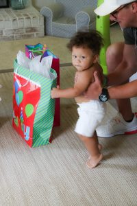 little boy with no shirt and white shorts at birthday