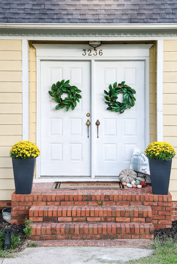 small front porch decorating ideas for fall with white double front door and mums on front porch