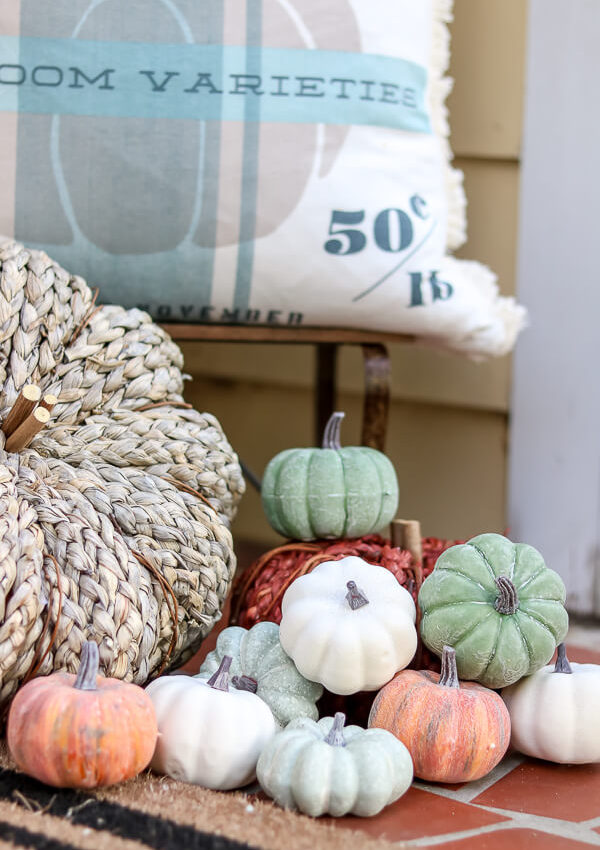 grouped mini pumpkins and straw pumpkin on small front porch