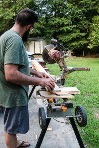 man with beard cutting lumber for DIY barn door