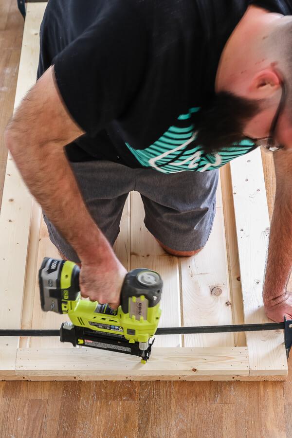 man with beard using Ryobi nail gun for DIY barn door