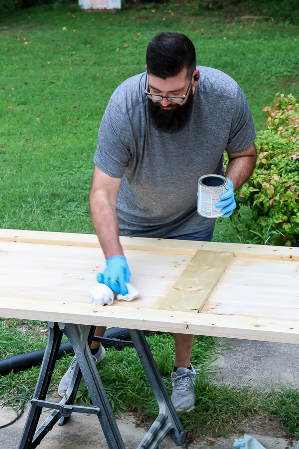 man with beard and blue gloves applying Varathane wood conditioner to DIY barn door