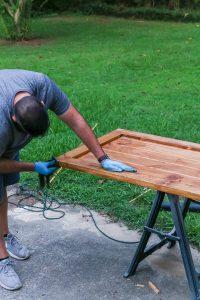 man applying stain to DIY barn door