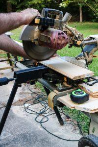 Man cutting lumber with a saw for DIY barn door