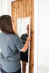 woman hanging mirror on a DIY barn door smiling