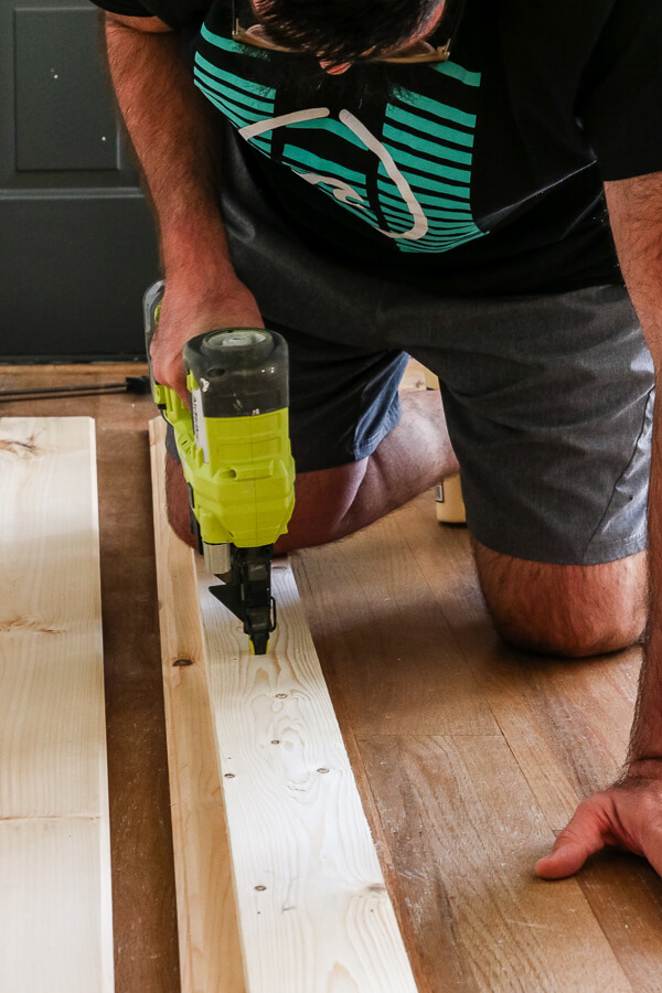 man with beard nailing wood together for DIY barn door plans