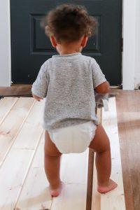 little boy in diaper walking on wood