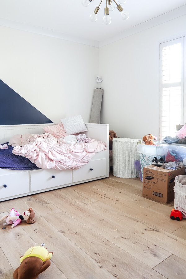 messy little girl's room with wood floors and Ikea bed in Sherwin Williams Alabaster white