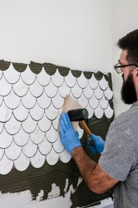 man setting wall tiles with rubber mallet and piece of wood