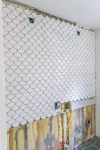 installing white mermaid tile on wall with black grout