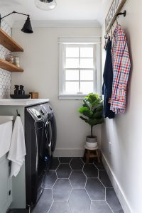 small laundry room space with tile floor and built in sink with hanging clothes on the wall